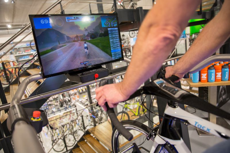 De Smart fietstrainers zijn ook nog aangesloten op Zwift of op Tacx Desktop App. Je kunt je vrienden dus in de superstore uitdagen voor een wedstrijd...